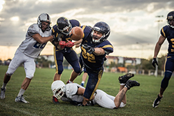 Image of football players being tackled to demonstrate emergency orthodontic care from Robinson Orthodontics