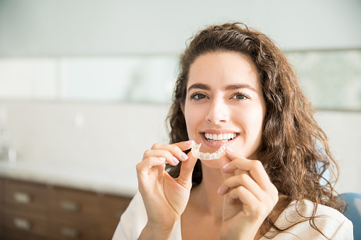 woman holding invisalign at Robinson Orthodontics in Grants Pass, OR