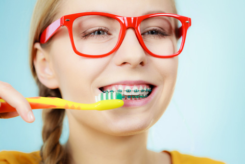 girl with brushing her teeth with braces at Robinson Orthodontics